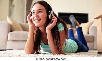 Pretty brunette relaxing on the rug listening to music at...