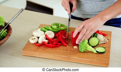 Pretty brunette preparing a healthy salad at home in the...