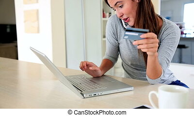 Pretty brunette using laptop to shop online while talking on...