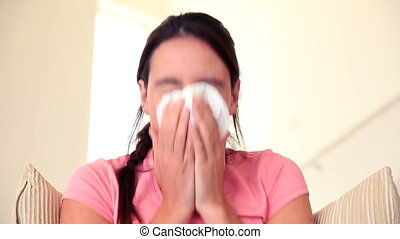 Sick brunette sitting on sofa sneezing at home in the living...