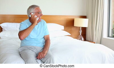 Senior man sitting on bed talking on the phone at home in...