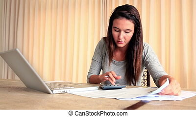 Stressed brunette working out her finances with laptop at...
