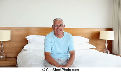 Senior man sitting on bed smiling at camera in the morning...