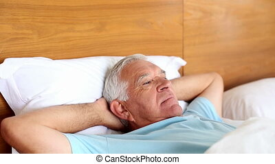 Senior man lying in bed sleeping at home in the bedroom