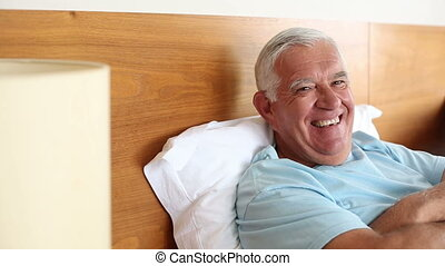 Senior man lying in bed smiling at camera at home in the...