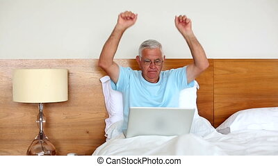 Senior man sitting in bed using laptop and cheering at home...