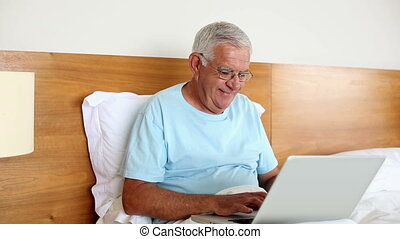 Senior man sitting in bed using laptop at home in the...