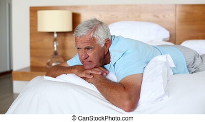 Senior man lying on bed thinking