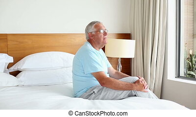 Senior man sitting on bed thinking at home in the bedroom