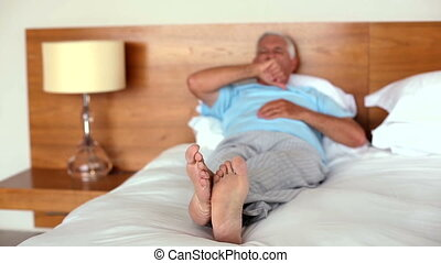 Senior man lying on bed yawning and stretching at home in...