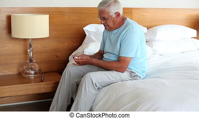 Senior man sitting on bed taking his medicine at home in the...