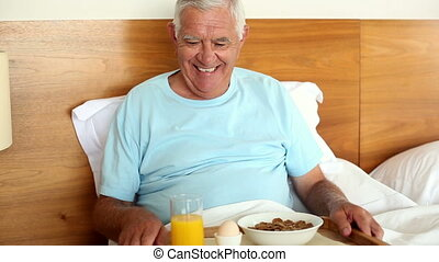 Senior man having breakfast in bed at home in the bedroom