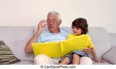 Senior man sitting on couch with his grandson looking at...