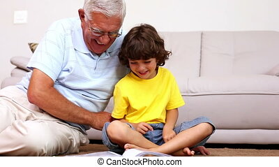 Senior man sitting on floor with his grandson looking at...
