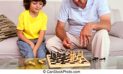 Senior man sitting on couch with his grandson playing chess...