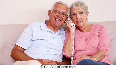 Senior couple sitting on sofa talking on the phone at home...