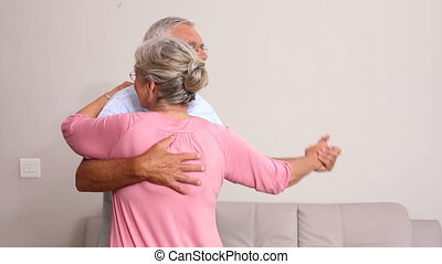 Senior couple dancing together at home in the living room