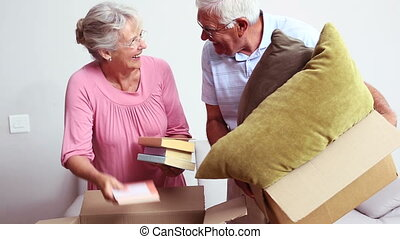 Senior couple packing their belongings at home in the living...