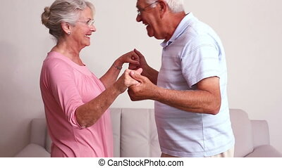 Senior couple hugging at home in the living room