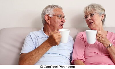 Happy senior couple drinking coffee on the couch