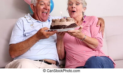 Senior couple celebrating a birthday on the couch at home in...