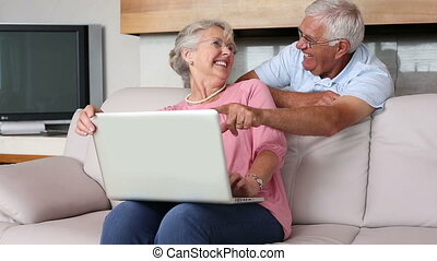 Senior couple using laptop together at home in the living...