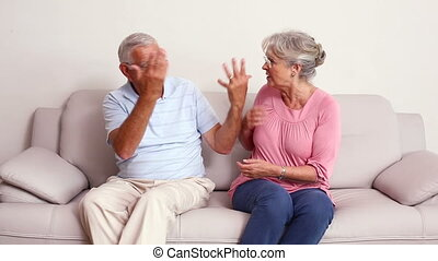 Senior couple arguing on the couch at home in the living...