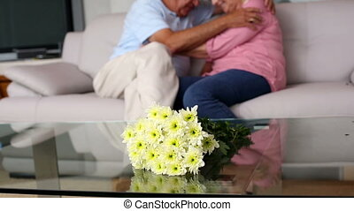 Senior couple cuddling on the couch at home in the living...