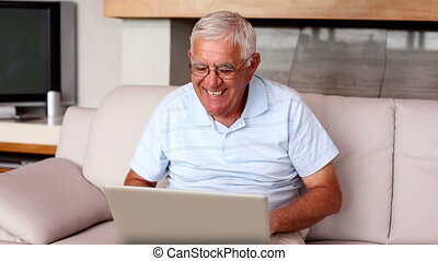Senior man using laptop on couch at home in the living room