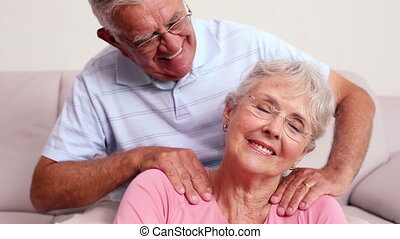 Senior man giving his wife a shoulder rub at home in the...