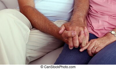 Senior couple holding hands on the couch at home in the...