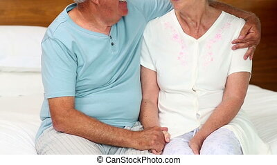 Senior couple sitting on bed chatting at home in the bedroom