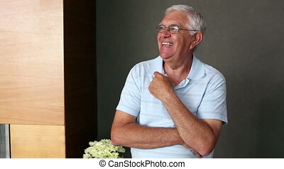 Senior man standing and smiling at camera at home