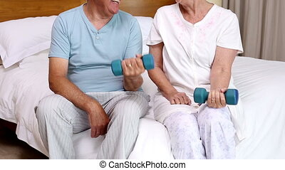 Senior couple sitting on bed lifting dumbbells at home in...