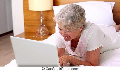 Senior woman lying on bed using la - Senior woman lying on...