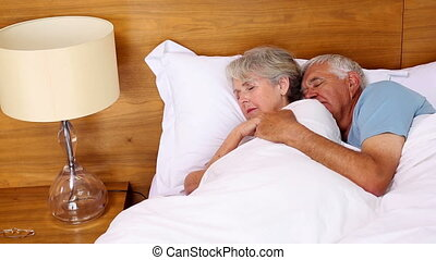 Senior couple sleeping in bed at home in the bedroom