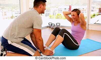 Happy fit woman doing sit ups with her trainer at the gym