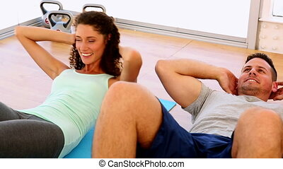 Happy fit couple doing sit ups together at the gym