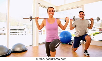 Fit couple doing lunges with barbells at the gym