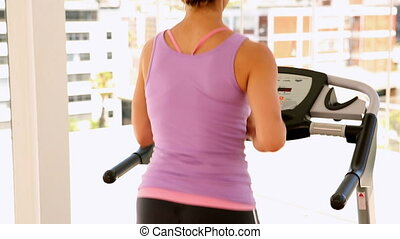 Fit woman running on treadmill
