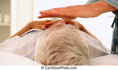 Senior man getting reiki therapy in therapy room