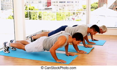 Three men doing push ups together at the gym