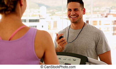 Fit woman running on treadmill with trainer timing her at...