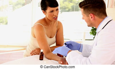 Dermatologist applying ointment to womans arm in his office...