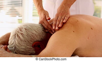 Senior man getting a massage in therapy room