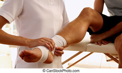 Man getting his ankle wrapped by the physiotherapist in...