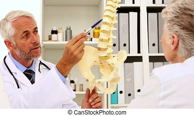 Doctor explaining a spine model to patient in his office at...