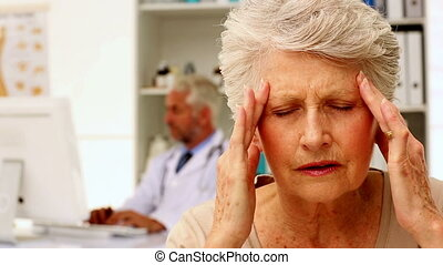 Senior woman with a bad headache visiting the doctor in his...