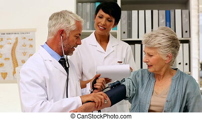 Doctor taking blood pressure of his patient with a nurse...