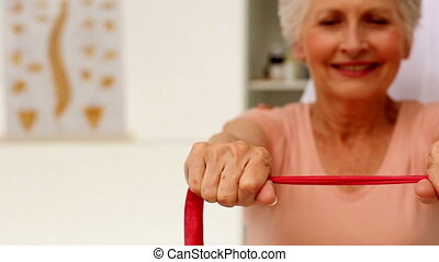 Nurse showing elderly patient how to use resistance bands -...